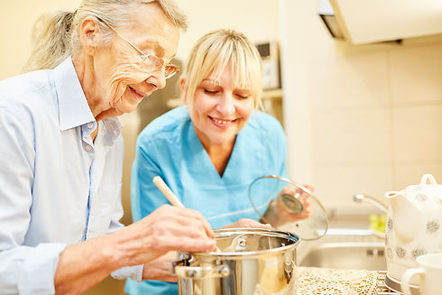 Nursing wife and senior citizen in the kitchen while cooking in assisted living.jpg