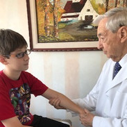 Dr. St. Amand examining Alex's forearm.