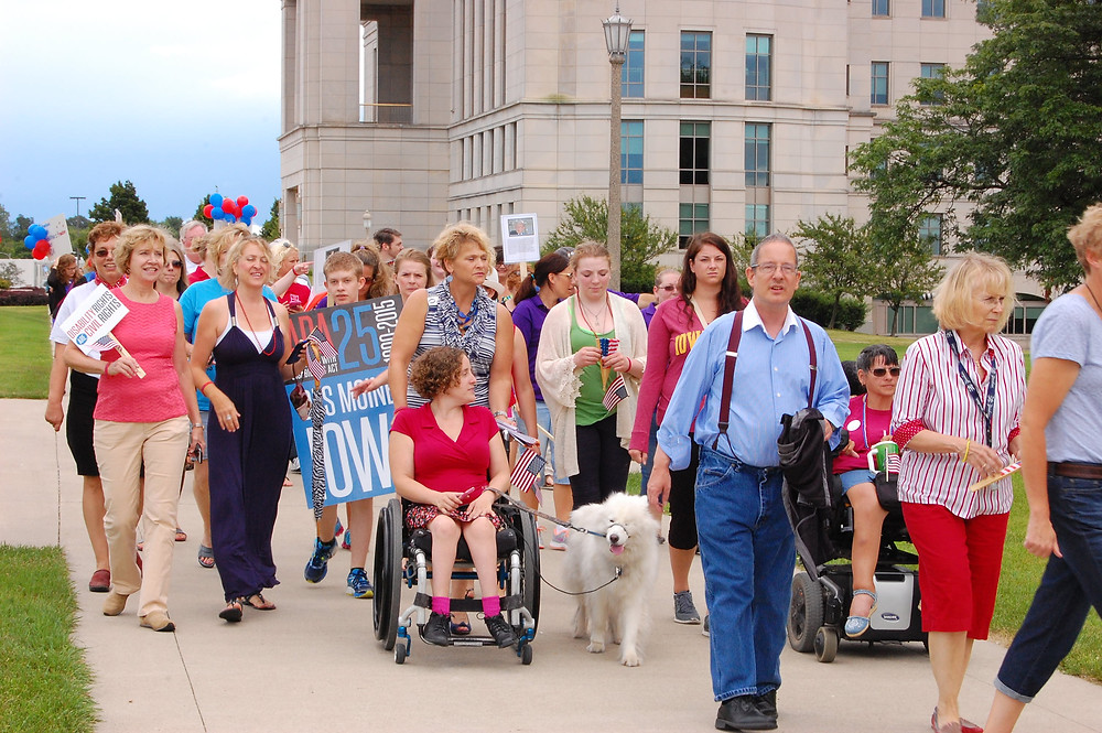 Dozens of marchers in Des Moines celebrate the ADA with signs and flags.