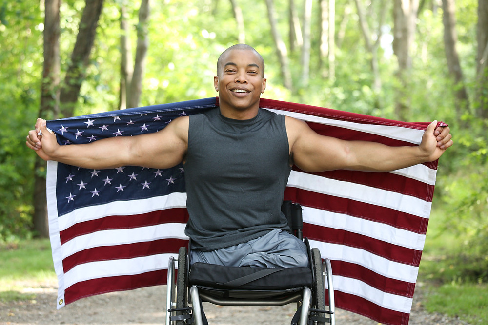 Man in wheelchair, holding an American flag, in a park.