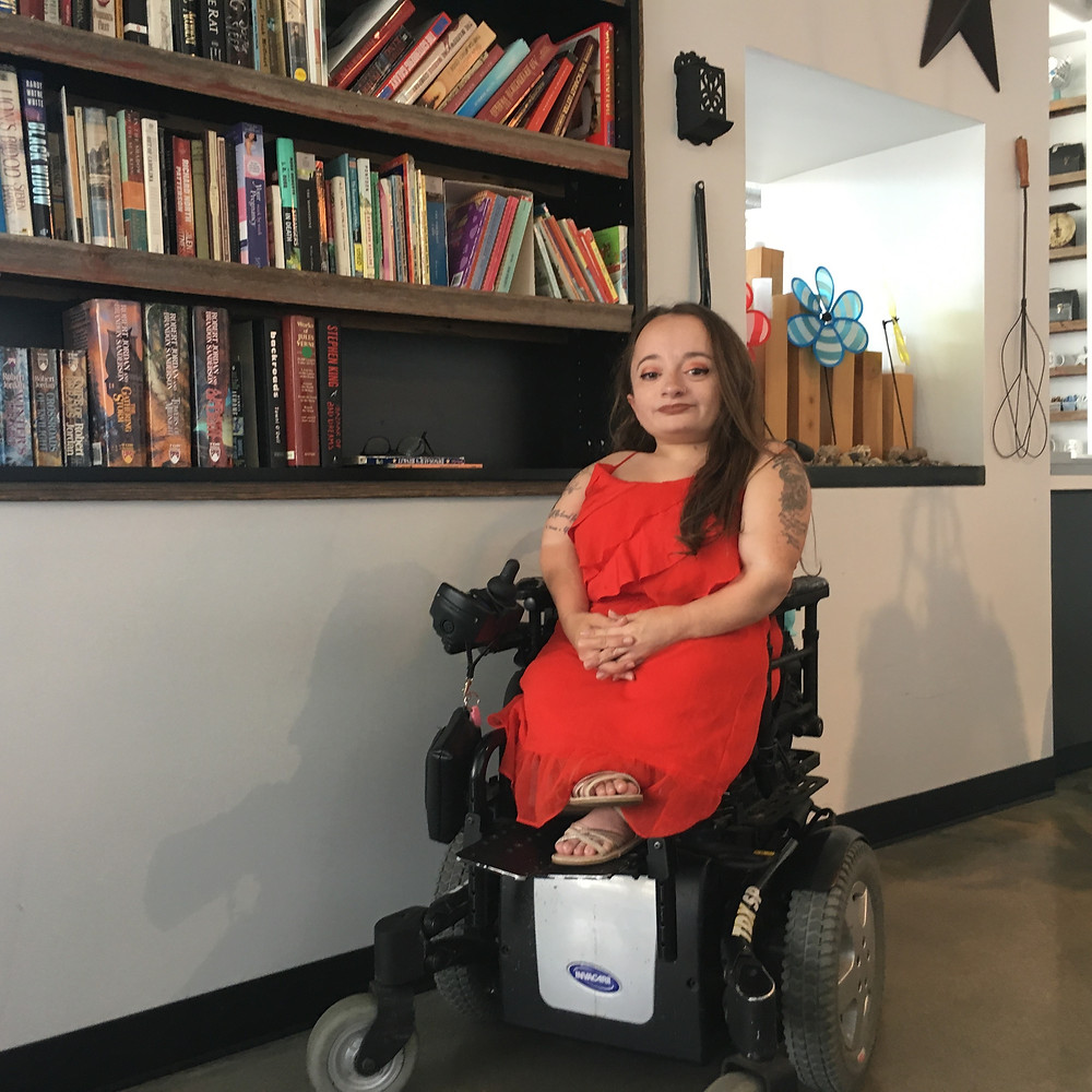 Heather Reimers in her power wheelchair and a fashionable red dress. Reimers sits with her hands folded and ankles crossed in front of a large bookshelf.