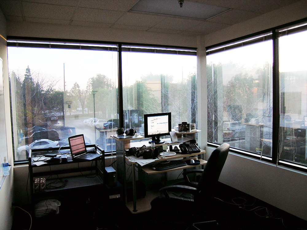 an office with two walls of windows and a messy desk
