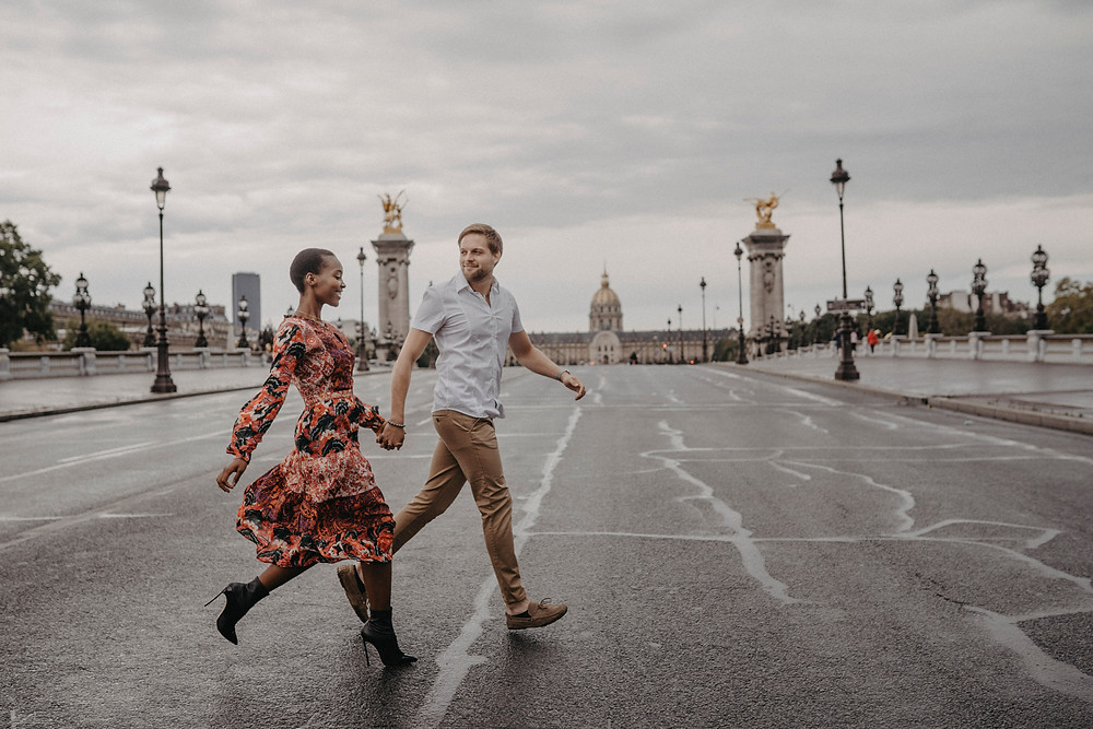 Interracial Couple running cross the street in Paris