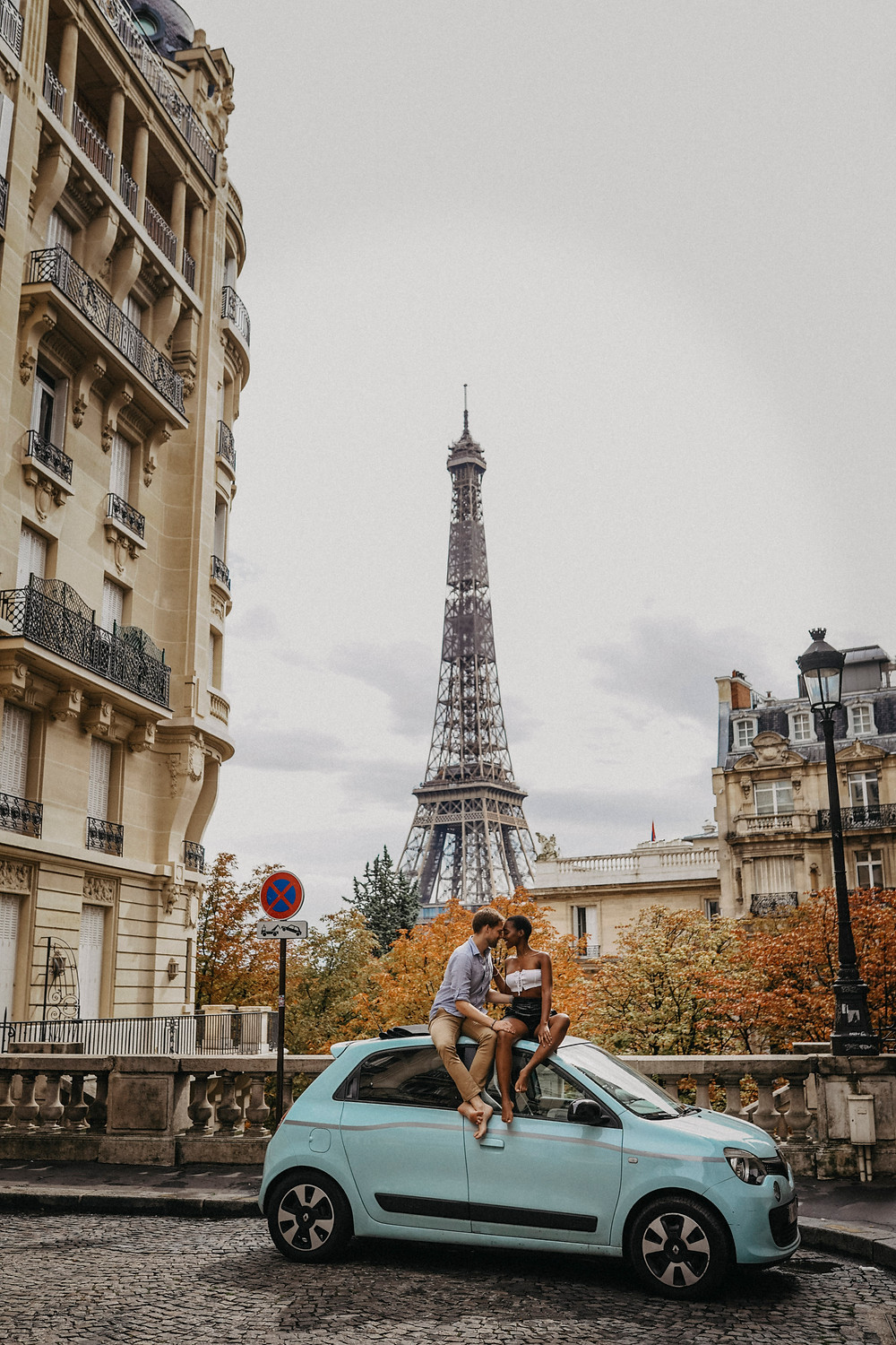 Interracial Couple Photos at eiffel tower sit on a car