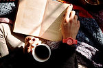 person-reading-book-and-holding-coffee-1