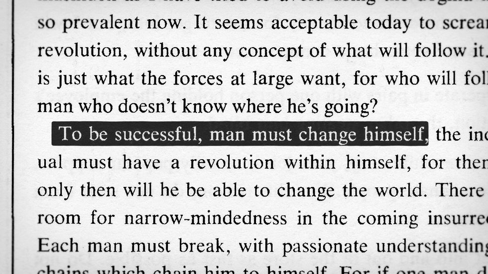 """""""To be successful, man must change himself"""" highlighted on a book page"""
