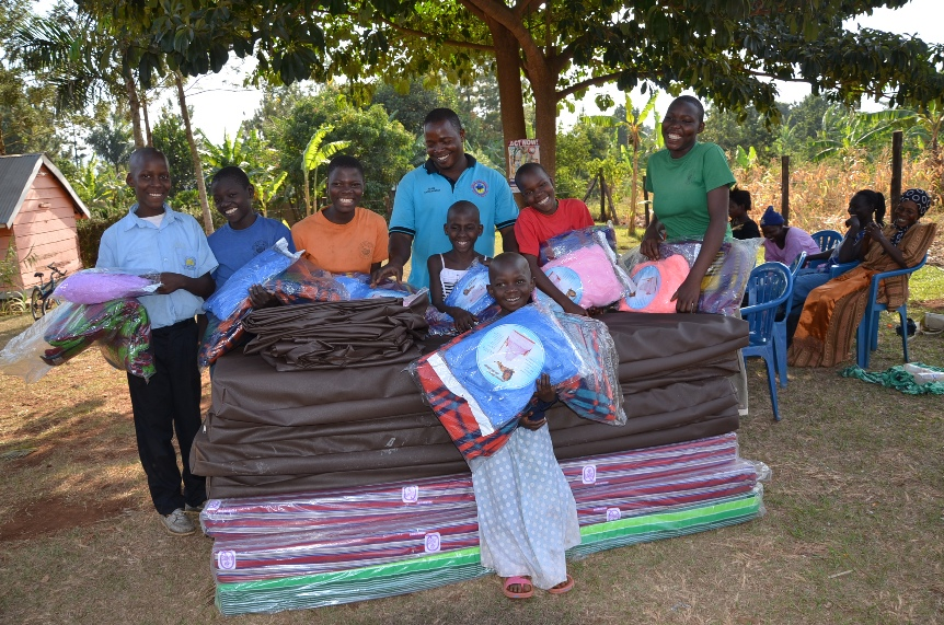 The children Mary, Judith, Apang, Kauthara, Shakira, Derrick and Catherine together with their parents expressing their happiness for the bed items given to them