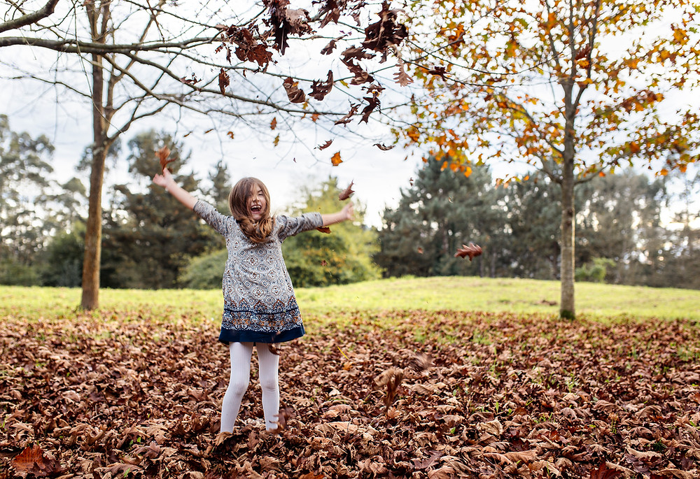 Girl playing in autumn leaves.