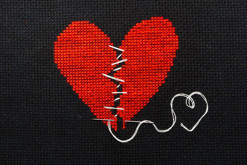 Broken heart embroidered with red thread