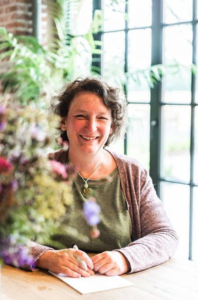 Claire Weiler omringd door bloemen kijkt in de camera