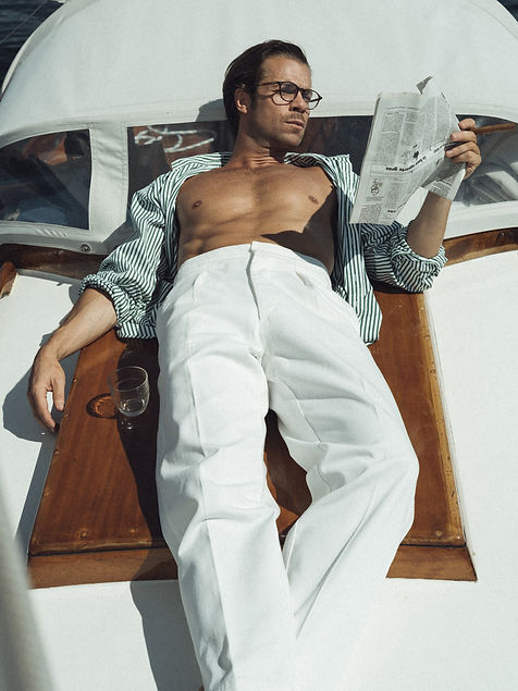 Pierre Saint Marie for Casatlantic wearing white cotton trousers. On deck of a vintage sailboat.
