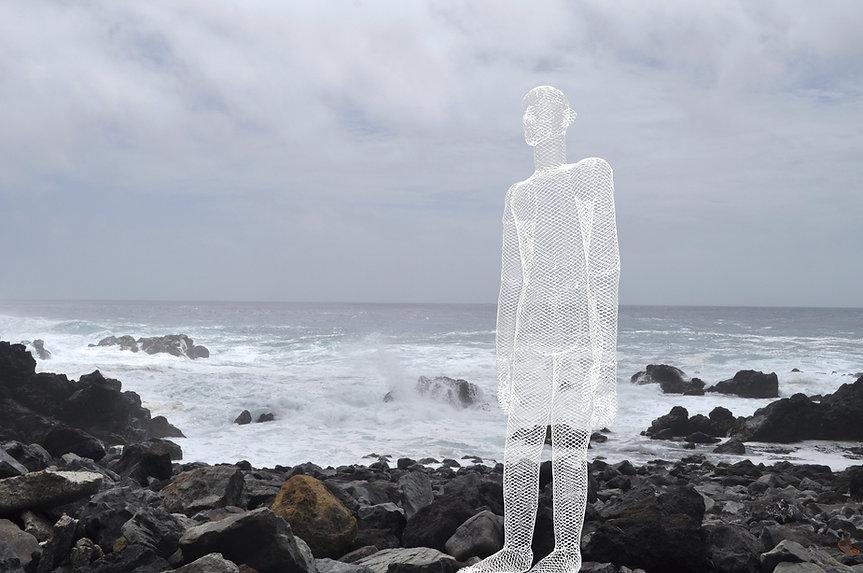 大島黒い岩の海岸に立つ.jpg