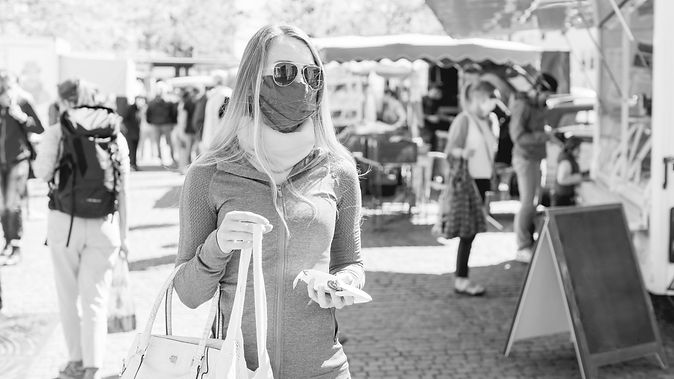 Woman at farmers market wearing a mask.