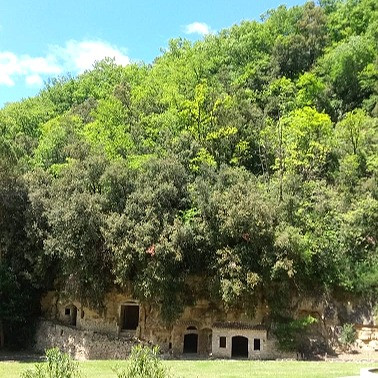 Le grotte scavate nell'arenaria presso i Frati Bianchi. Sul versante, fascia di lecci, dal verde scuro direttamente sulla roccia e specie di latifoglie autoctone caducifoglie, verde brillante