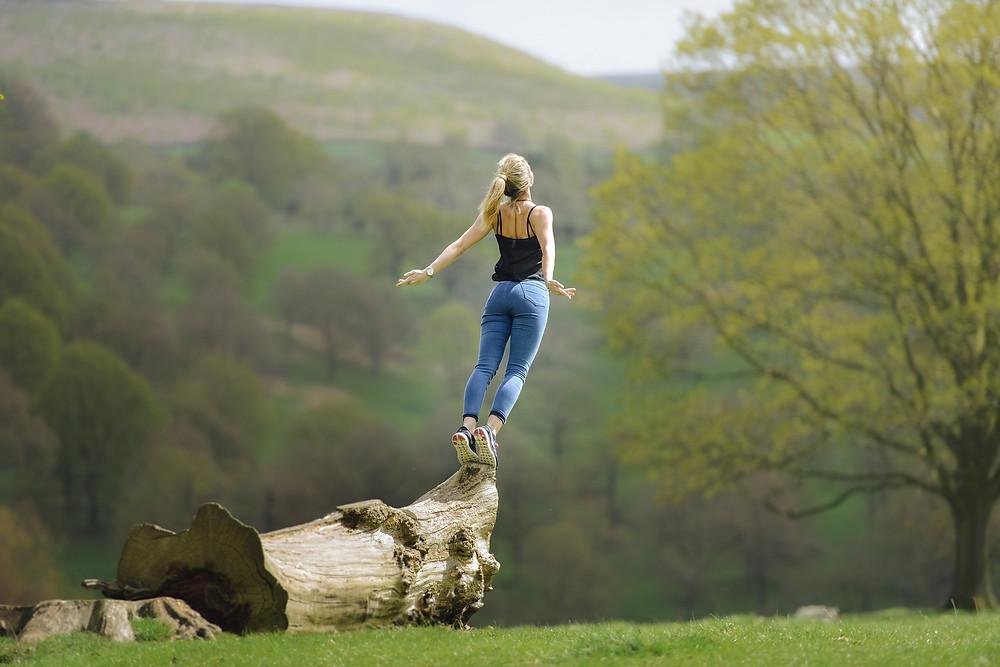 Une jeune femme méditant sur le bout d'un tronc