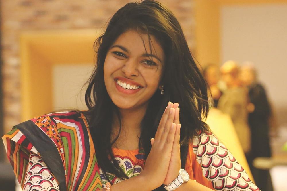 Une jeune femme joint les mains, signe de remerciement