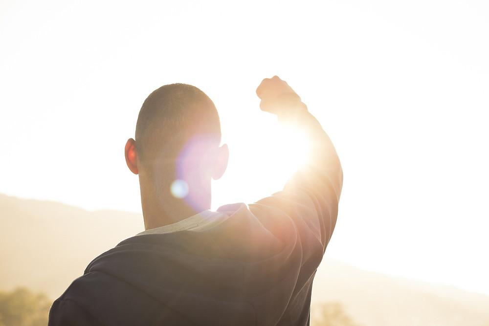 Un homme levant son bras droit en direction du Soleil