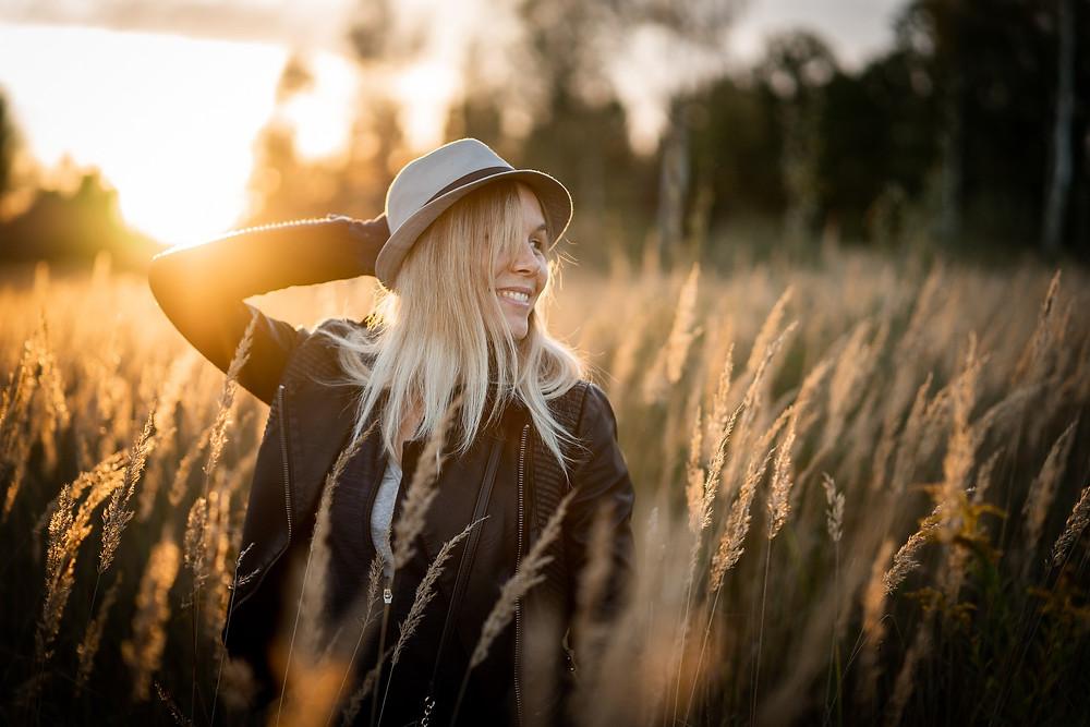 Une jeune femme blonde souriant dans un champ de blé