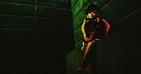 Film Still: Divine Decadence, Darling, director, Kristina Steinbock. A blond haired woman sits on a ledge in Cabaret attire, looking into the camera. The walls around her are tinged in green, as she wears a black bola hat, a corset, and black fishnet tights.