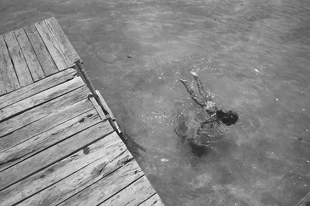 a kid floating in the warm water of Bacalar's blue lagoon. a Magnificent photo of humor and excitement.