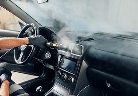 Carwash, worker cleans salon with steam