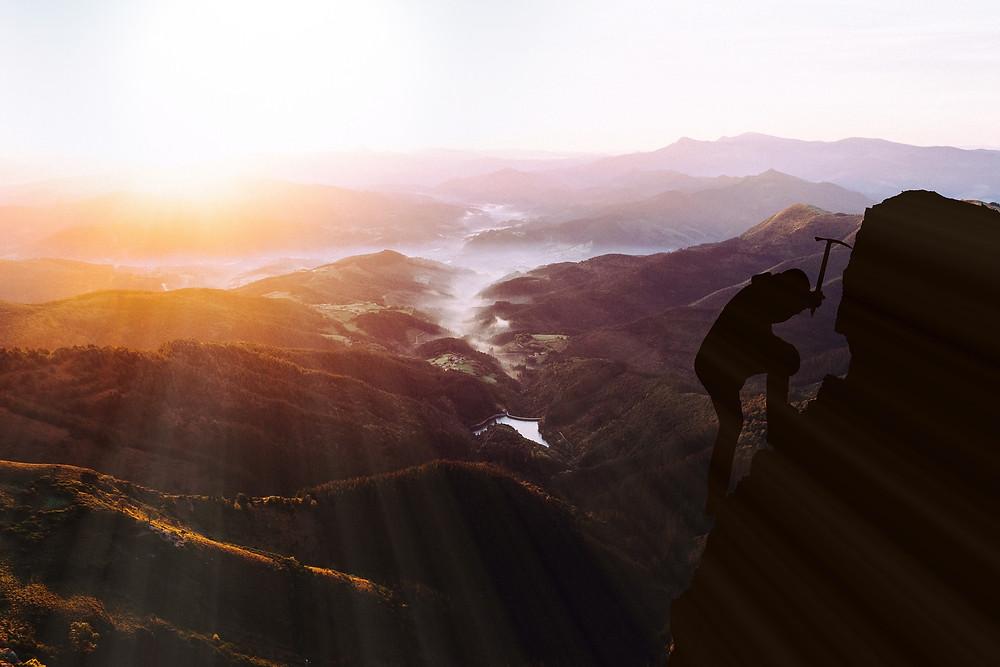 Person Climbing Mountain With an Axe