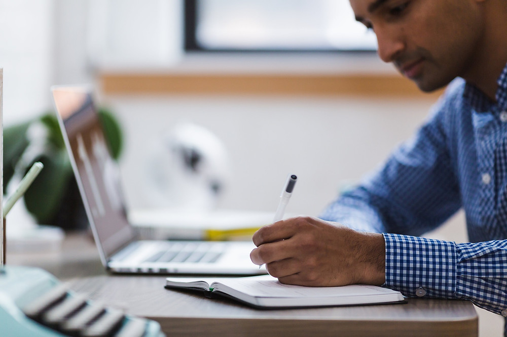 Black Man Working at Desk with Notepad and Laptop