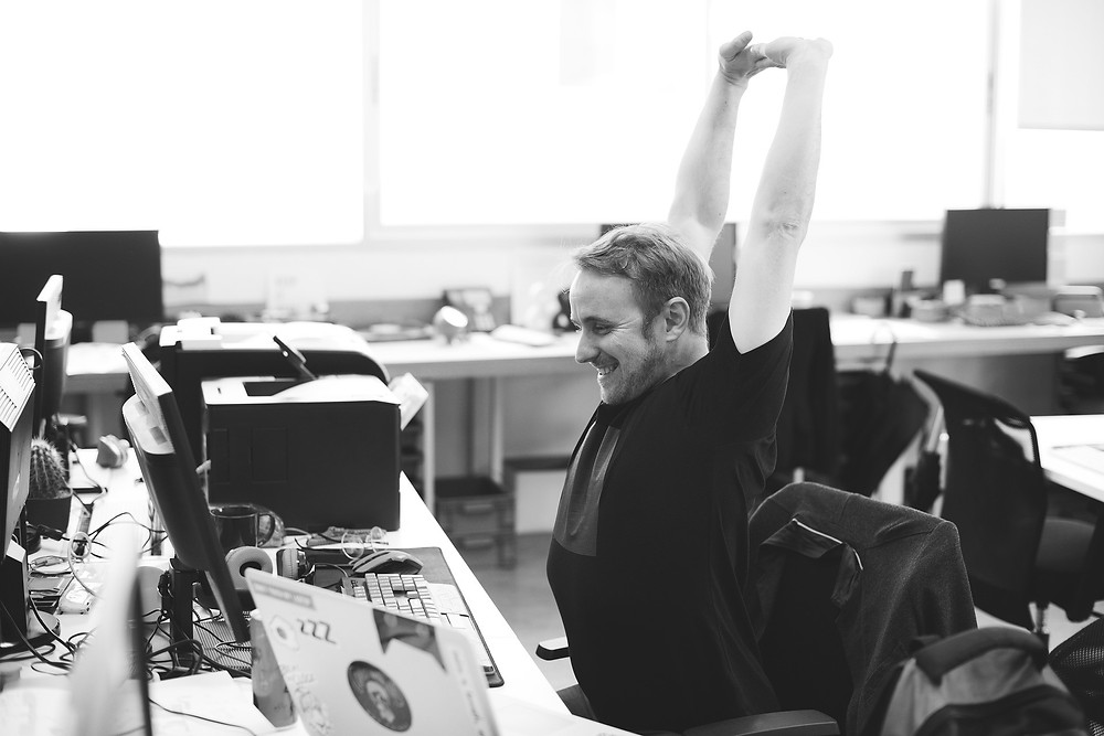 Man stretching at desk and smiling