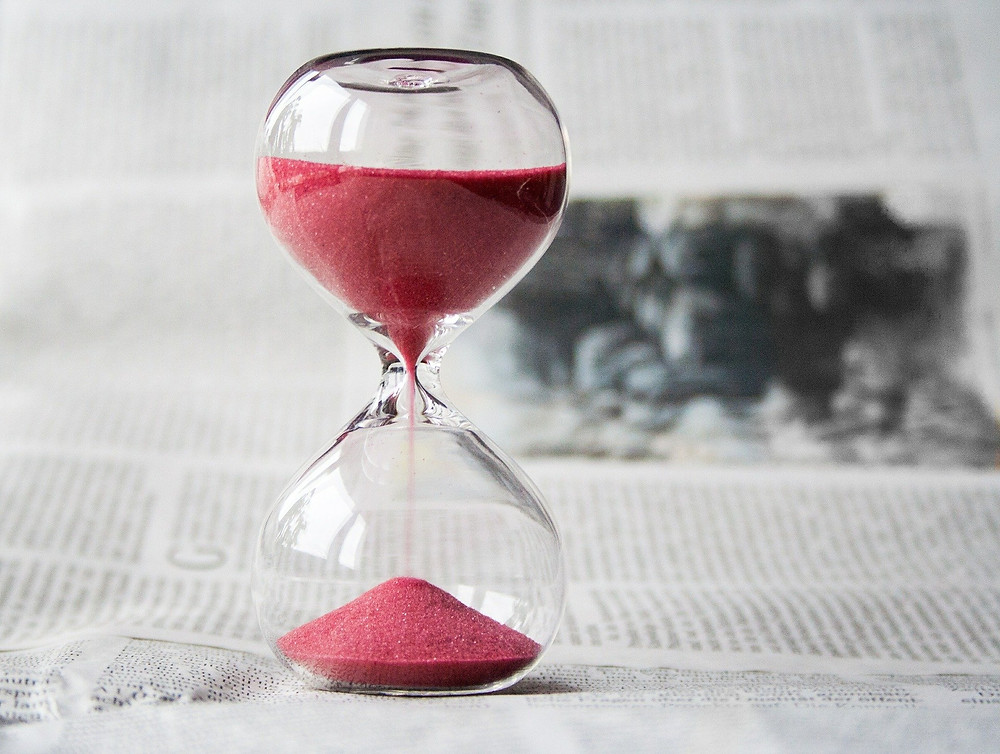 Hour Glass with Sand Flowing on a Newspaper