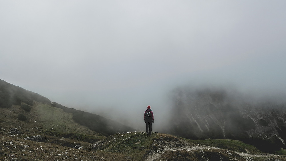 Man Looking Upon a Foggy Mountain