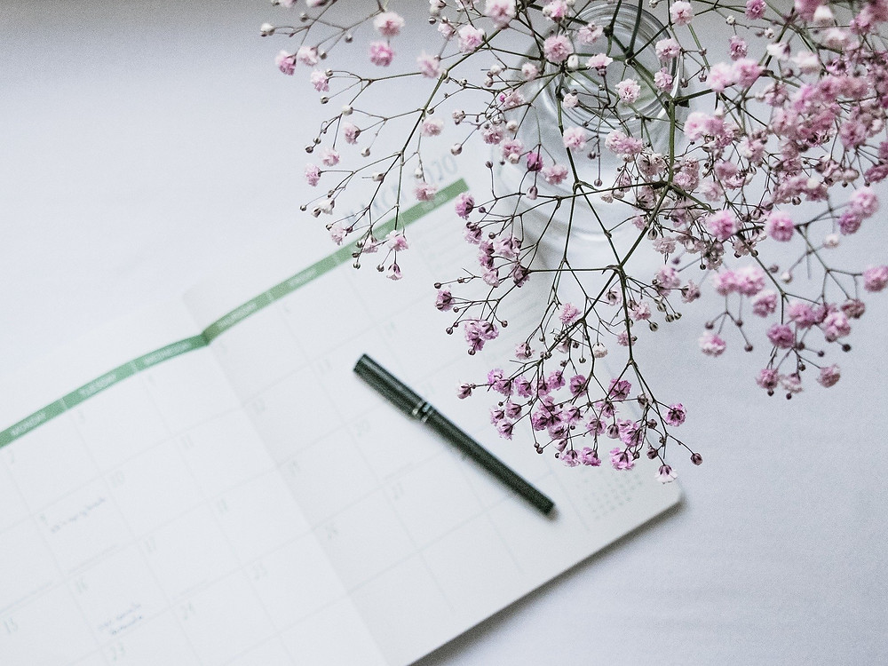 Planner with Pen and Flowers on a Desk