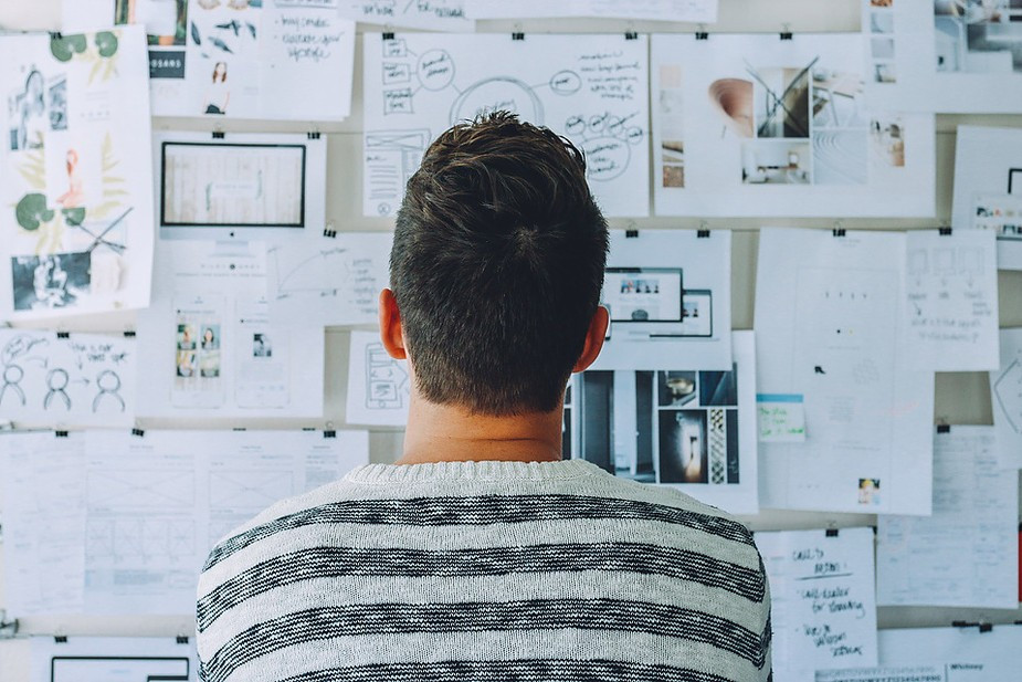 Man Looking at Board With Plans and Papers Hung Up