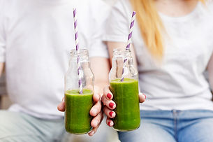 Young couple drinking green smoothie. Man and woman holding green vegetable smoothies. Hea