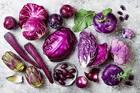 Raw purple vegetables over gray concrete background. Cabbage, radicchio salad, olives, koh