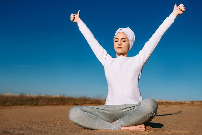 On a sunny afternoon in the sand a girl in white clothes is sitting and practicing yoga, r