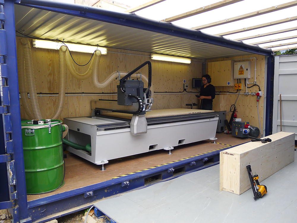A shipping container with a CNC router inside.