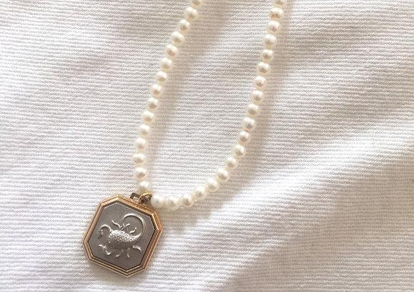 Collier plaqué or orné d'une médaille Scorpion et de perles