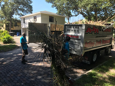 Action Junk Removal workers loading dump truck with storm damage brush and debris