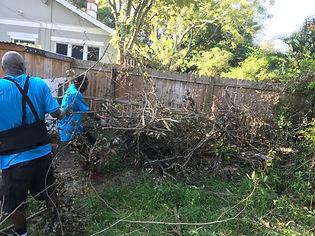 men remove brush pile from hurricane storm damage