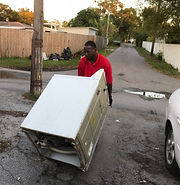 Action Junk Removal worker removing a washer with a dolly truck in Clearwater Fl.