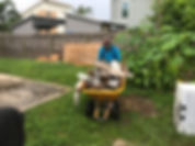 Action Junk Removal worker with wheelbarrow full of debris