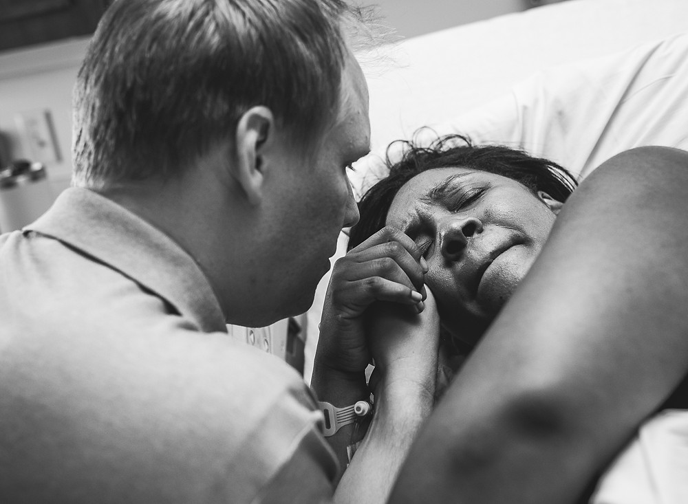 birth photographer captures tender moment between mom and dad during labor in Oklahoma City at mercy hospital