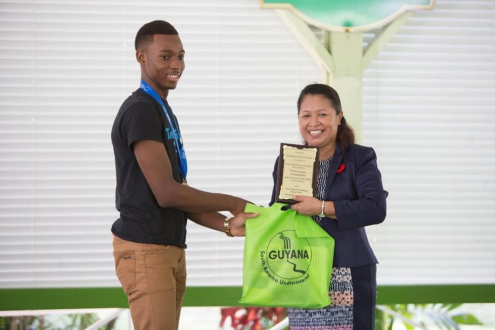 Team STEM Guyana member receiving an award on behalf of the Team.