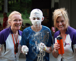 Two women and a camper with whip cream on his face