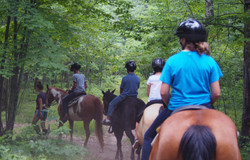 Campers horseback riding in the woods
