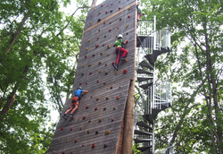 Campers climbing rock-climbing wall