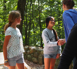 Counselor shaking hand of young girl