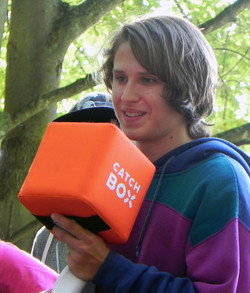 Camper holding orange box
