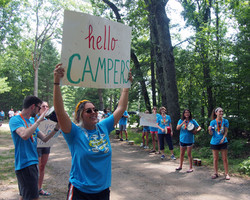 Camp counselor holding welcome sign
