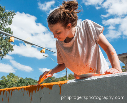 Assistant Aime Polivka adding drip rainbow to path side of wall